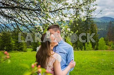 Standing on sunny outdoor background in the green mountain landscape, telling someting to the girl ear. Back view