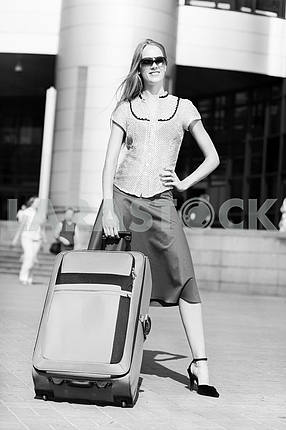 Beautiful girl with a suitcase against the backdrop of the stati