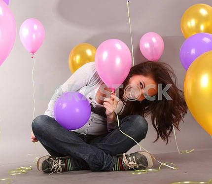 Happy beautiful young woman smiles at background balloons