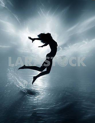 Black and white picture of a naked girl jumping out of the water