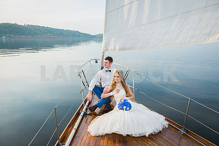 Honeymoon sailing - Stylish young bride and groom sitting on the nose of board the sailing yacht