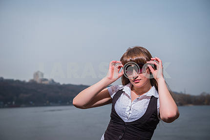 Girl with sunglases Women holding the sunglasses with light brown hair, dressed in white and black, portrait, sunny day, with river and the city on the background