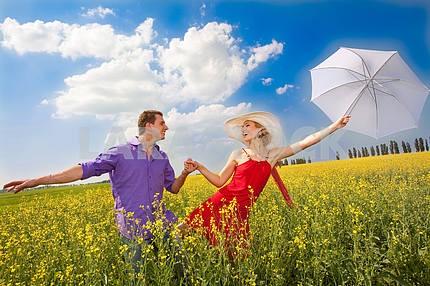 Молодые любители мальчик и девочка , держась за руки . Девушка вылетает в зонтик .