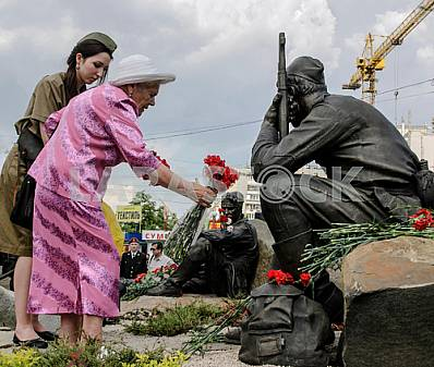 Old woman lays flowers at the monument to fallen soldiers in May 2012