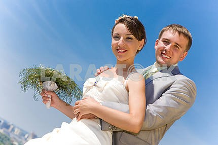 Portrait smiling groom and bride against blue sky