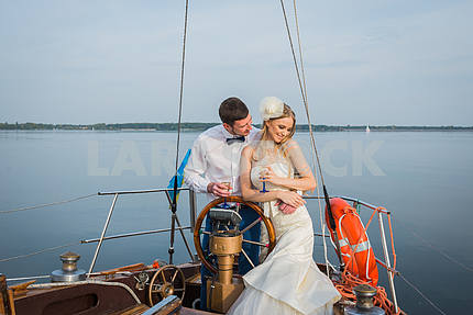 Happy bride and groom drinking champagne on a sailing yacht. happy together.  The steering wheel of the yacht.  wedding on the sailing yacht