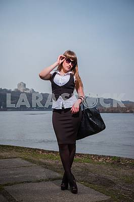 Business woman dressed in black and white, with the black bag, in sunglasses, city and river on the background