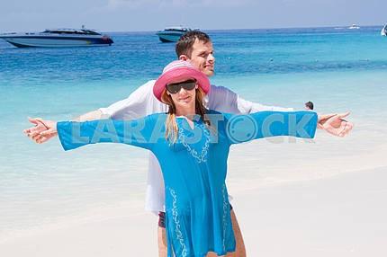 Молодые любви пара, улыбаясь в голубое небо на море, пляж