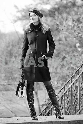 Beautiful blonde in coat and hat standing outdoors