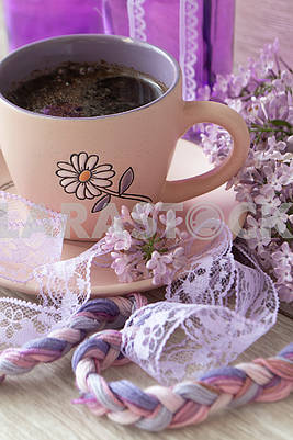 Branches and flowers of lilac with purple petals. Cup with coffee, cocoa, spring breakfast. Vintage
