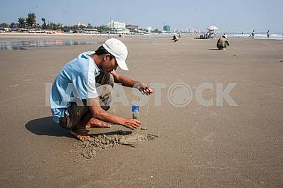 Fisherman catches in the sand worms for fishing