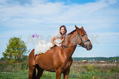 Bride brown-haired woman on a horse, in wedding dress, forest and blue sky on the background
