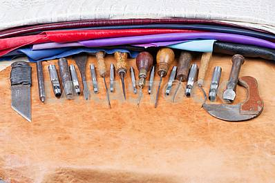 Leather craft tools on a leather background. Craftsman work desk . Piece of hide and working handmade tools on a work table. Top view. Copy space