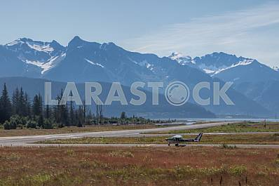 The plane on the runway in the mountains