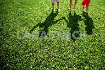 Kids with their shadows on grass. silhouettes of three persons standing with their hands stretched up