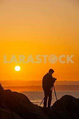 Photographer is standing on the Pacific coast at sunrise