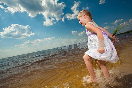 Cute girls play in the waves on sea