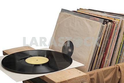 Retro styled image of a collection of old vinyl record lp's with sleeves on a wooden background. Copy space