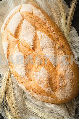 Freshly baked traditional bread with golden ears, vertical image