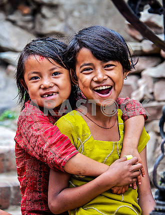 Two girls sincerely smile at the camera