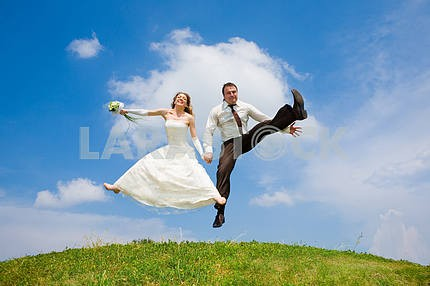 Groom and bride jumping against backdrop a sky and trees. In all