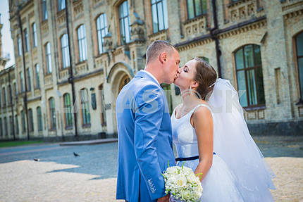 Bride and groom, on the street, green tree and architecture building on the background, kissing each other, wedding day