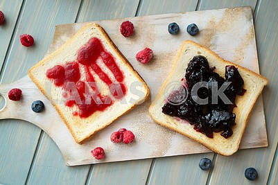 Homemade confiture with fresh fruits from garden, rustic decoration. Fruit jam on toasted bread. Top view