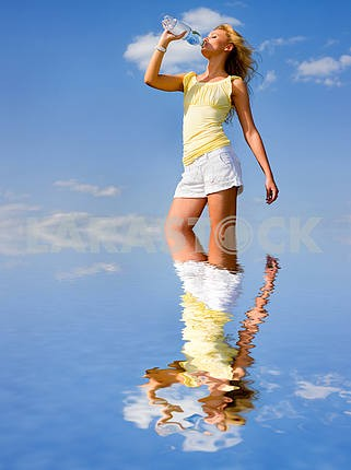 Beautiful girl drinking water under blue sky. Reflected in the w