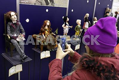 The girl photographed on a mobile phone doll on the stand