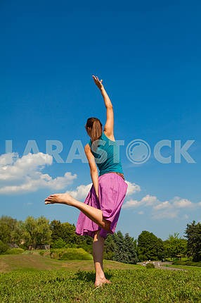 beautiful young girl dancing barefoot on the grass