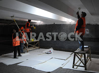 Employees of public services paint the ceiling