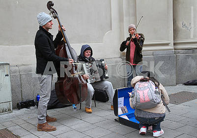 The girl chooses a disk from street musicians