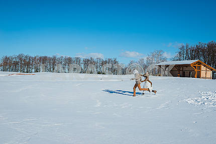 A wedding couple running on the snowed field on a sunny day  rustic style wedding brown colors and white wedding dress