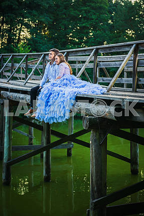 A love story couple, in love, together in the forrest park, sitting on the end of  wooden bridge, girl in a beautiful violet dress, sunny evening, summer, green water on the background