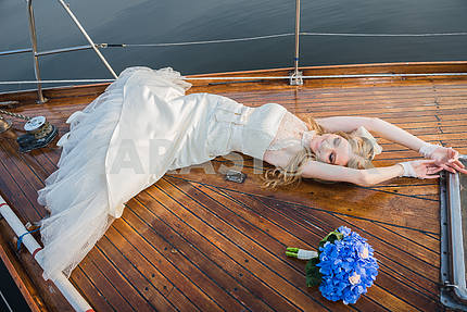 Happy honeymoon sailing - Stylish young beautiful bride laying on the wooden board the sailing yacht - happyly lookin