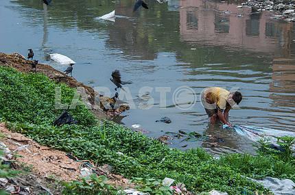 Парень стирает ткань в мертвой реке Багмати.