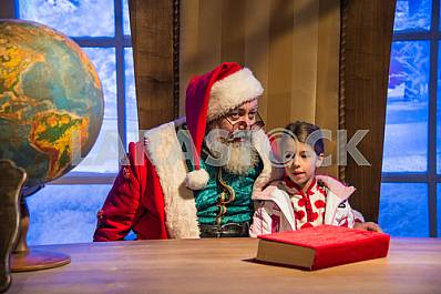 Santa Claus holding a little girl in her arms in front of his de