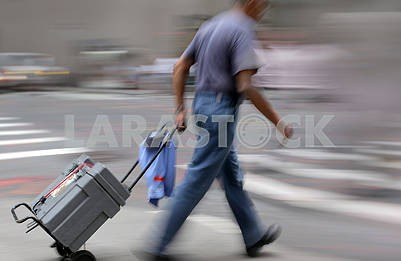 A man with luggage trolley walking down the street