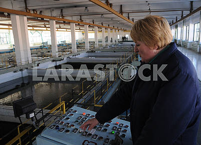 Employee of Desnyanskaya waterworks station behind the control panel