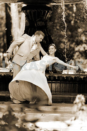 Groom and the bride joy against backdrop fountain. In all growth