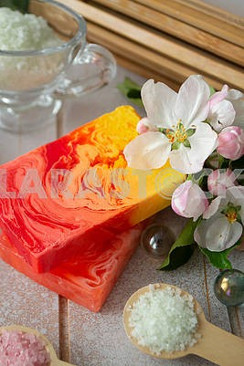 Bar of natural soap with bath sea salt and pink sakura flowers.