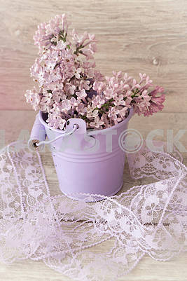 Blooming lilac bouquet in violet bucket shaped vase on light wooden background. Vintage