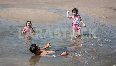Two girls and dad are swimming in shallow water