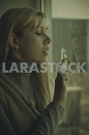 Beautiful girl sitting on a window sill at the window