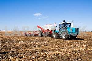 Tractor spraying field with sprayer