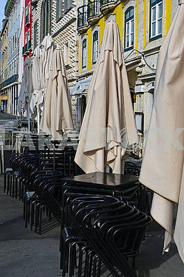 Folded umbrellas, chairs and tables of the restaurant