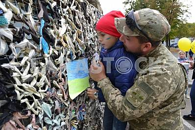 Military and child visiting a camouflage net