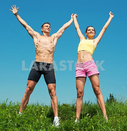 Young athletic Couple smiling under blue sky