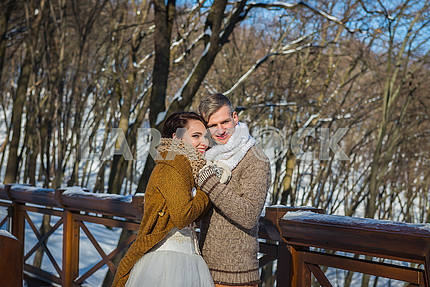Wedding couple in a showy wither day, holding each other, rustic style  short wedding dress. Girl brunette. beautiful bride winter lanscape on the background