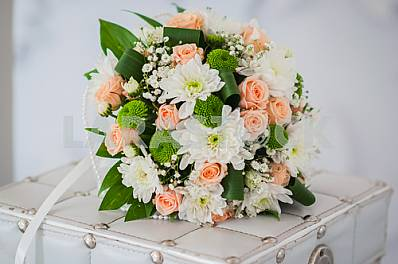 Wedding bouquet made of roses, chrysanthemum and laying on the white box